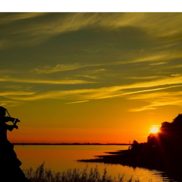 woman playing fiddle in the sunset